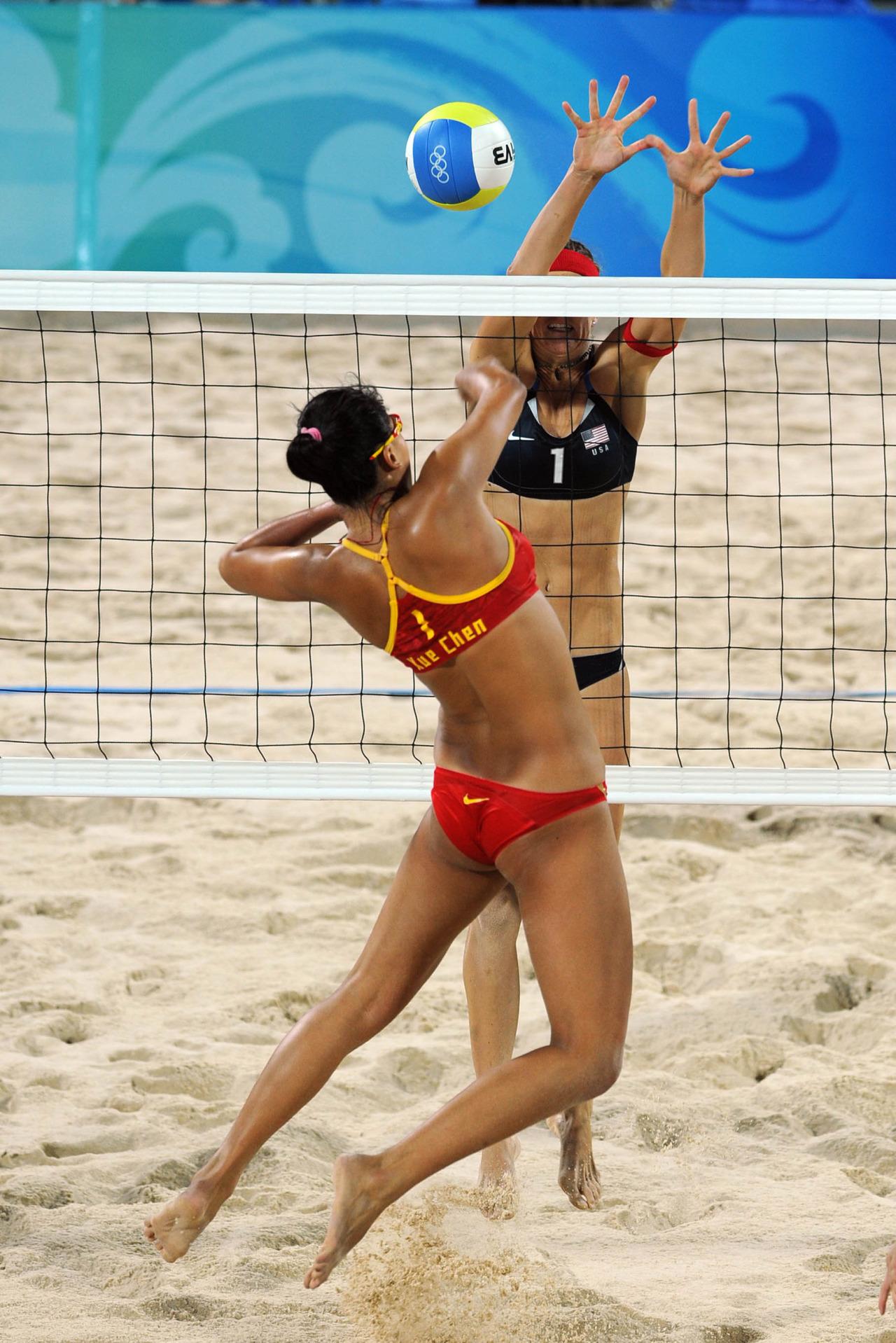 Xue Chan  (CHN) spikes against Nicole Branagh (USA)