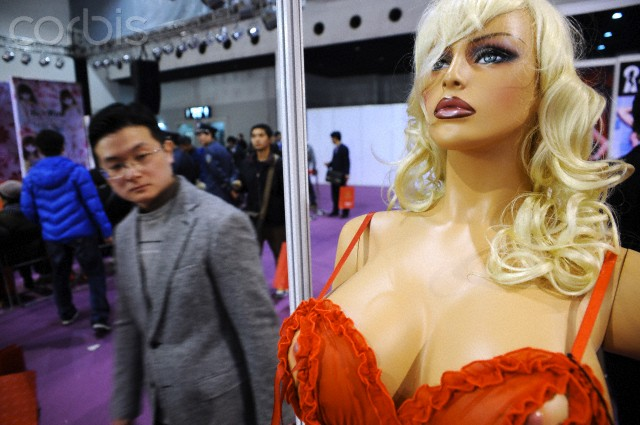 11 Mar 2011, Shanghai, China --- A visitor looks at an inflatable sex doll during the China Adult-Care Expo 2011 in Shanghai, China, 11 March 2011. China is the worlds largest manufacturer of sex toys, over 70% of the worlds marital aids are produced in China, according to surveys. China has over 1,000 sex toy manufacturers, a statistic researched and released by the China Market Research center. In the past few years, annual production output for sex toys in China has reached over US$2 billion. --- Image by © Imaginechina/Corbis